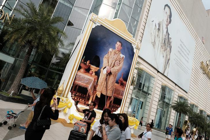 People walk past a portrait of Thailand's King Maha Vajiralongkorn Bodindradebayavarangkun and late King Bhumibol Adulyadej at a department store in central Bangkok